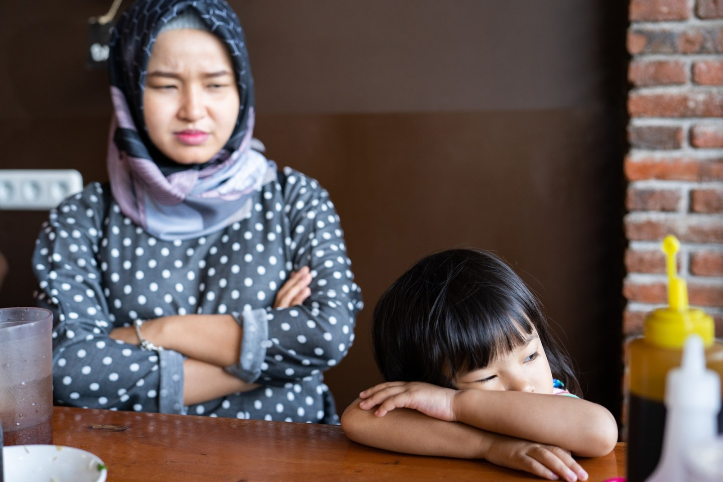 upset child. portrait of sad kid and mad, mother at the back looking at her