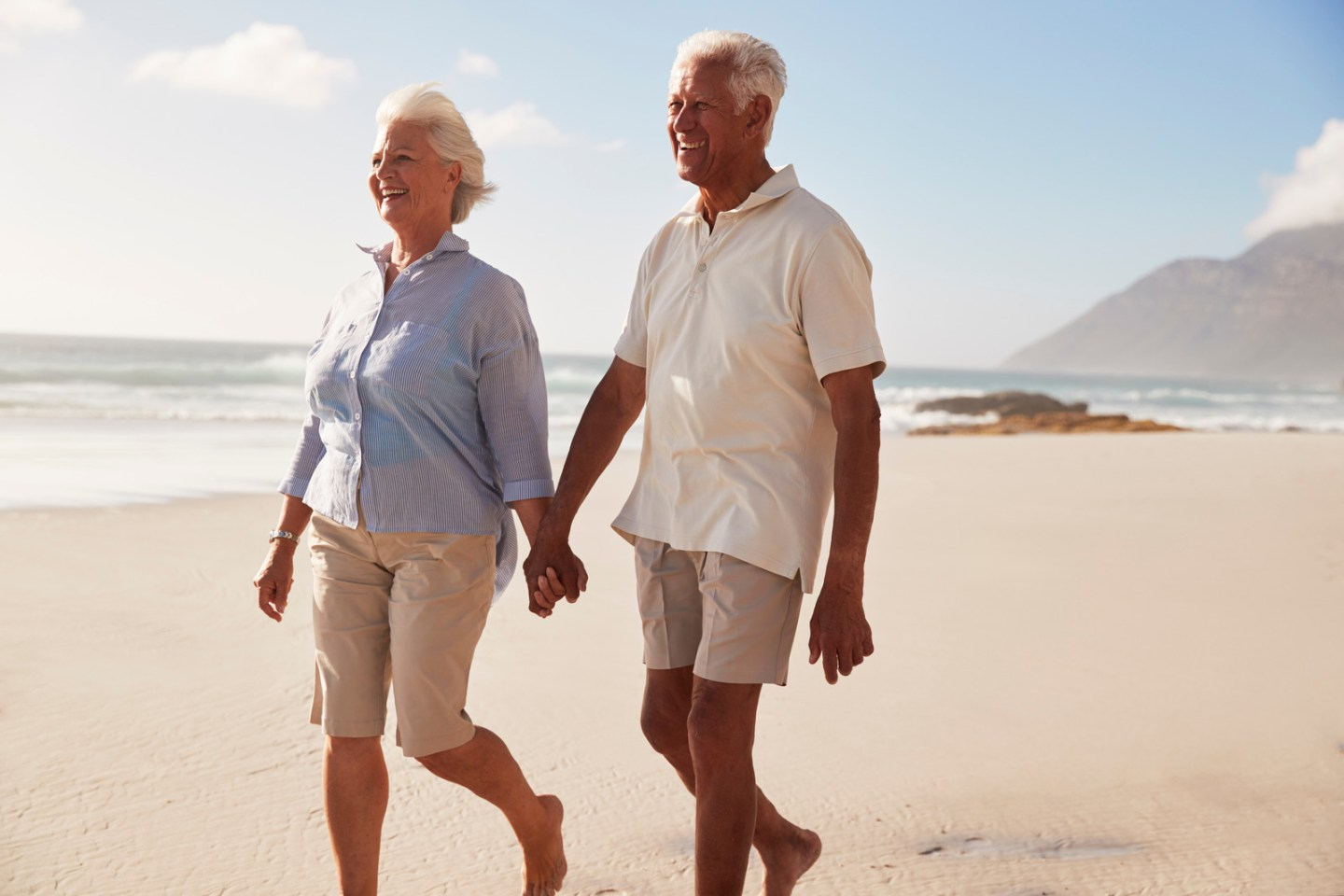 Senior Retired Couple Walking Along Beach Hand In Hand Together