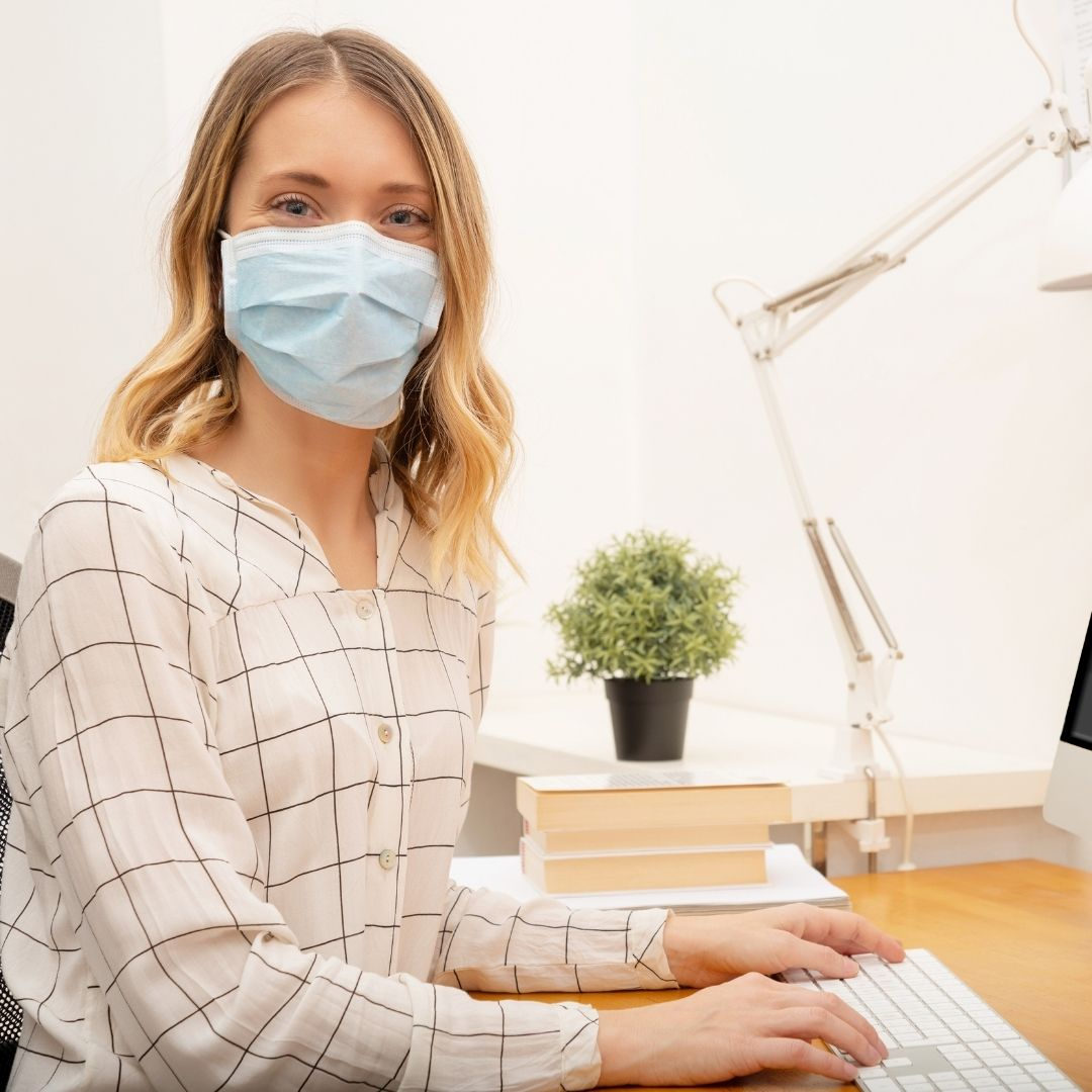 businesswoman working from home wearing protective mask