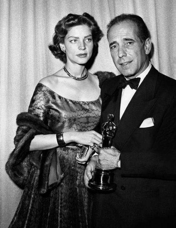"""LOS ANGELES - MARCH 20: Married actors Humphrey Bogart and Lauren Bacall pose for a portrait at the Academy Awards ceremony which was held at the RKO Pantages Theater on March 20, 1952 in Los Angeles, California. Bogart holds the Oscar he won for best actor in John Huston's film """"The Afircan Queen."""" (Photo by Frank Worth, Courtesy of Emage International/Getty Images)"""