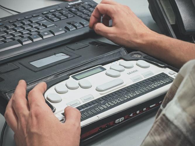 Blind man using braille screen reader