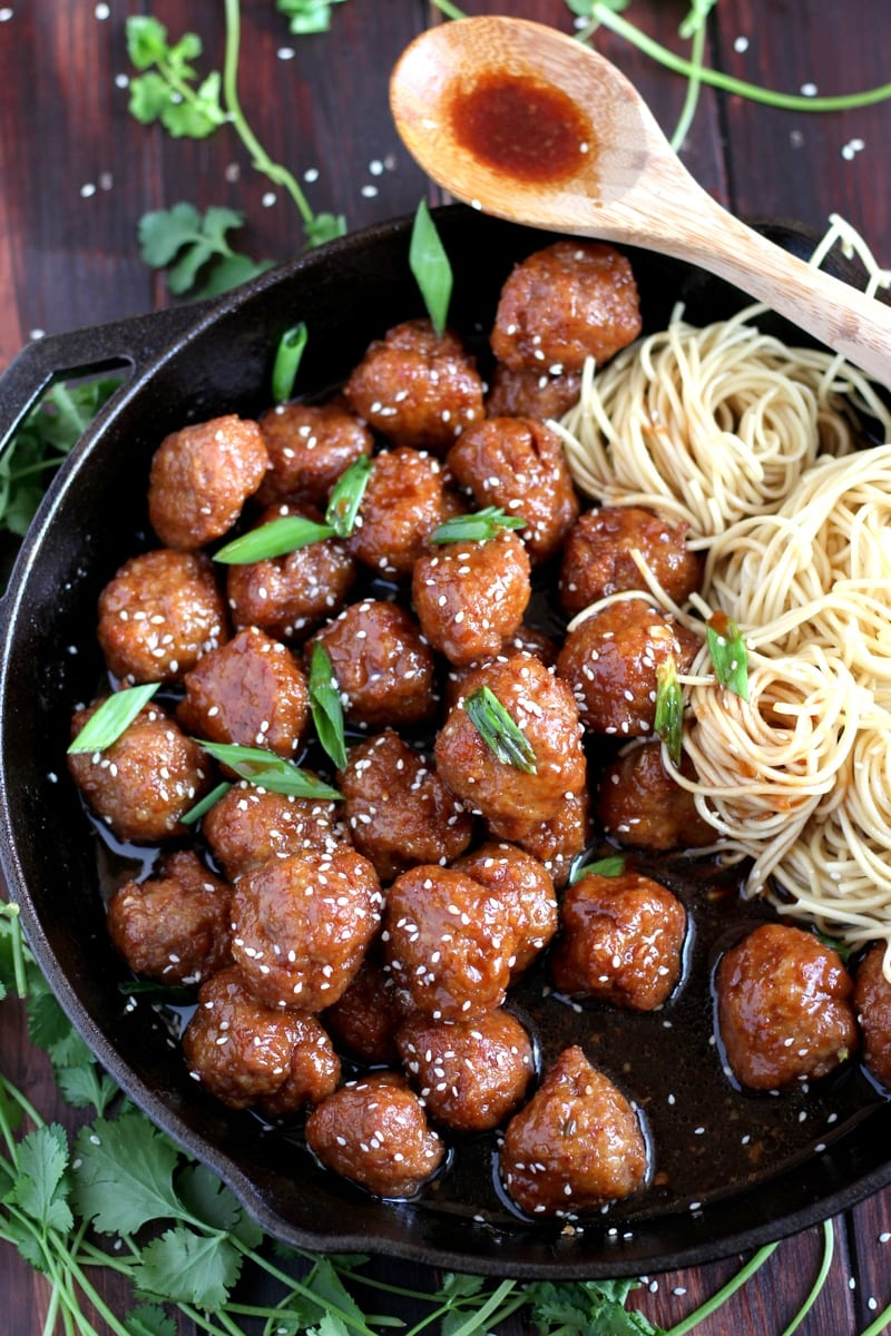 Sesame Soy Ginger Meatballs + Noodles. Easy to make meatball recipe, baked in a soy ginger sauce served over chow mien noodles. thewoodenskillet.com #foodphotography #meatballs