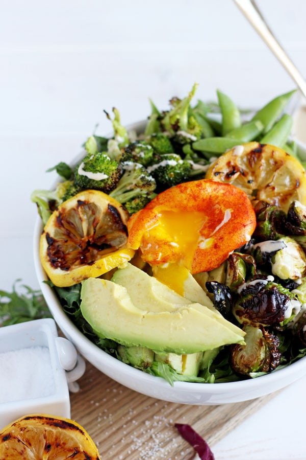 Healthy Spring Green Salad + Turmeric Poached Egg. The perfect vegetarian salad for lunch or dinner! Made with avocado, Brussel sprouts, pea pods and broccoli and all drizzled with tahini dressing! So good for you and delicious! thewoodenskillet.com