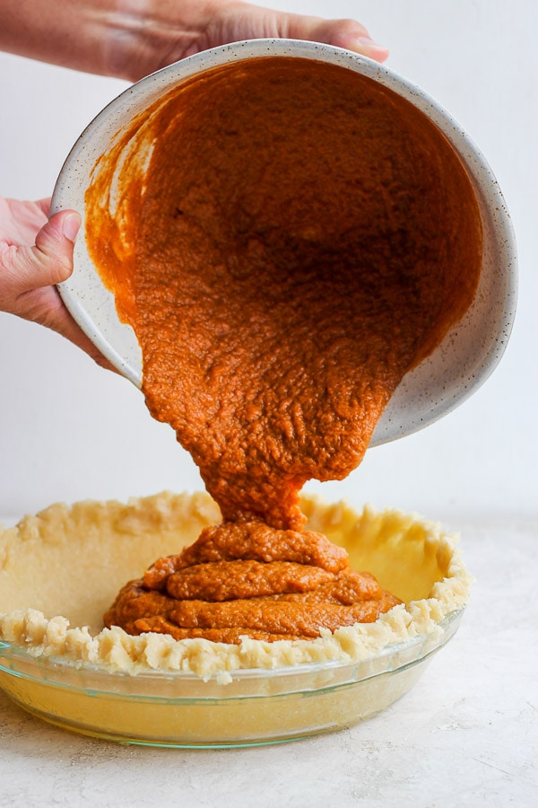 Two hands holding a bowl pouring pumpkin pie puree into a pie crust.