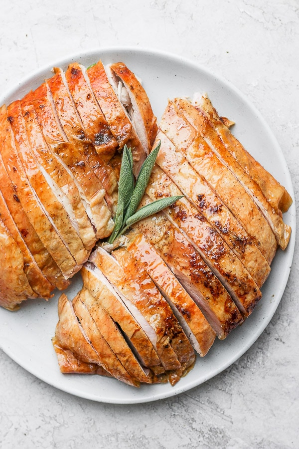 Plate with two turkey breasts sliced with a sprig of fresh sage.