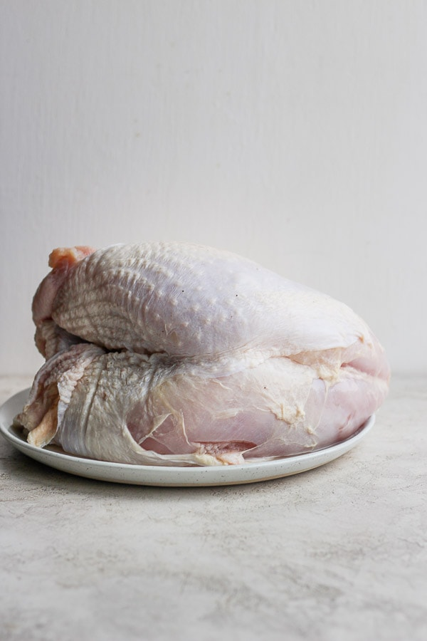 Turkey breast (raw) sitting on a plate.
