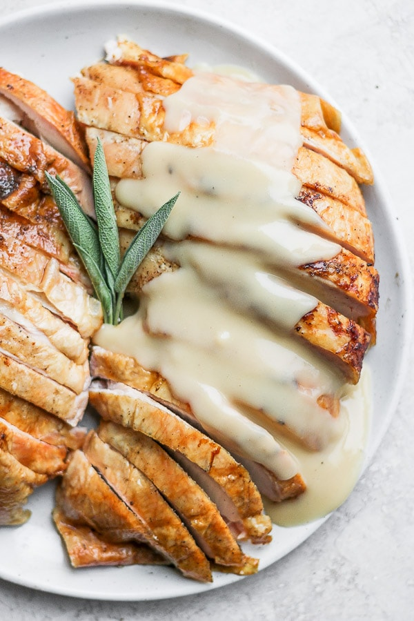 Plate with two turkey breasts sliced with a sprig of fresh sage and gravy drizzled on top.