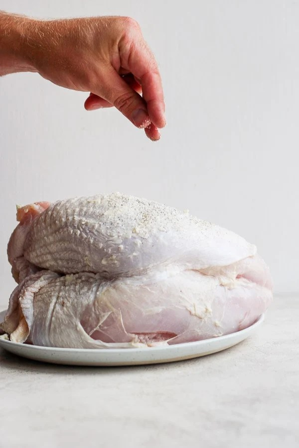 A man's hand sprinkling salt and pepper on a raw turkey breast.