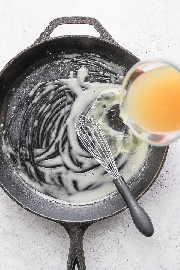 Cast iron skillet with a whisk combining melted ghee and tapioca starch and chicken broth being poured into the pan.