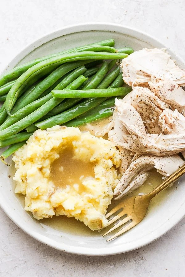Plate filled with steamed green beans, mashed potatoes and gravy and chicken.