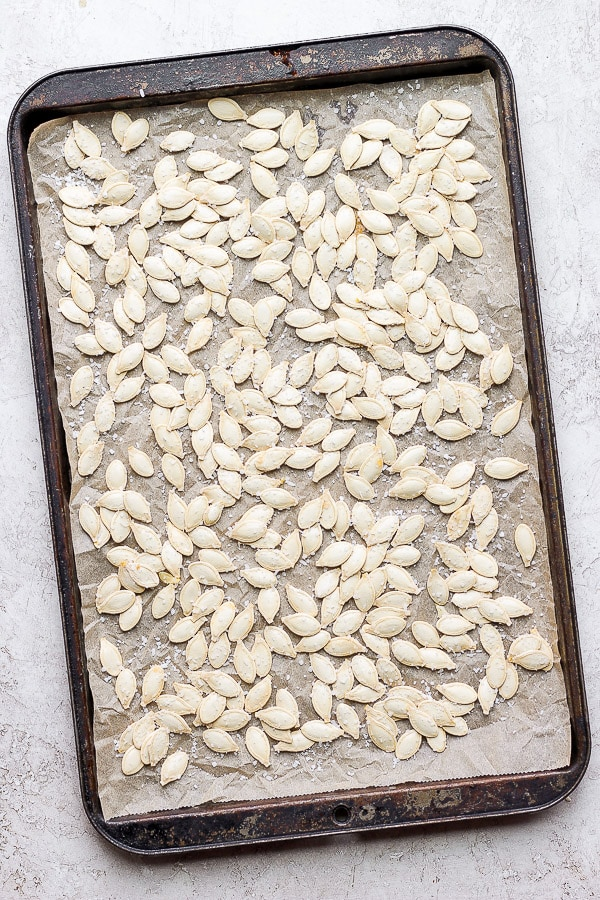 Rinsed pumpkin seeds on a parchment-lined baking sheet and sprinkled with generous amounts of salt.
