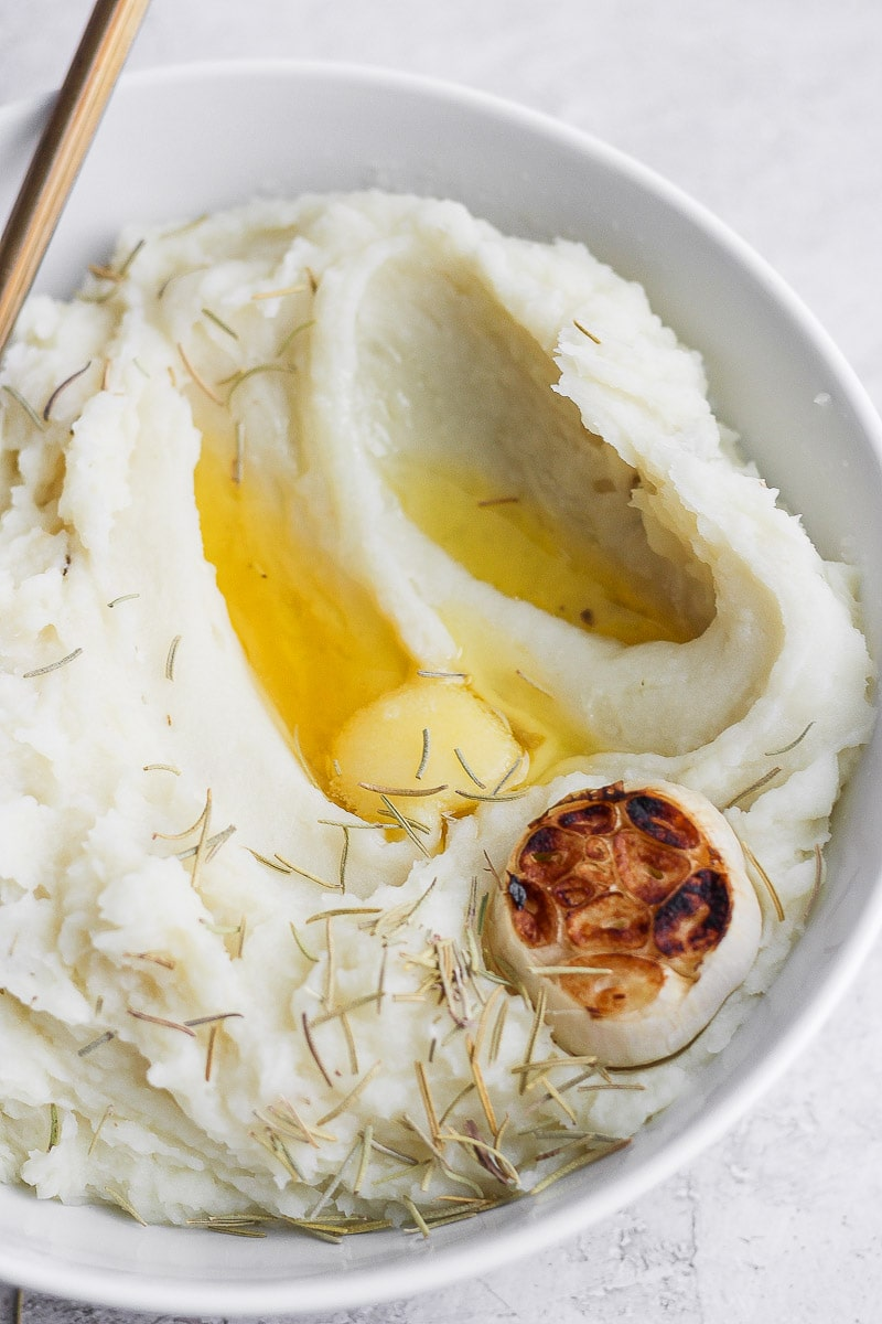 A bowl of mashed potatoes with melted ghee, a head of roasted garlic, rosemary, and a spoon.