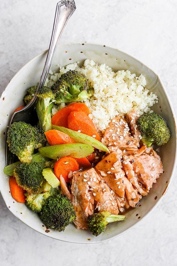 Bowl of teriyaki salmon with vegetables and cauliflower rice.