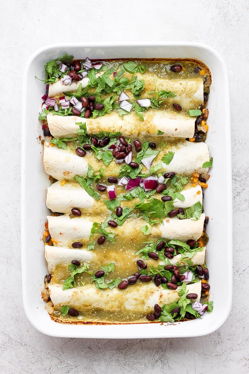 White casserole dish filled with cooked vegan enchiladas and topped with black beans and fresh cilantro.