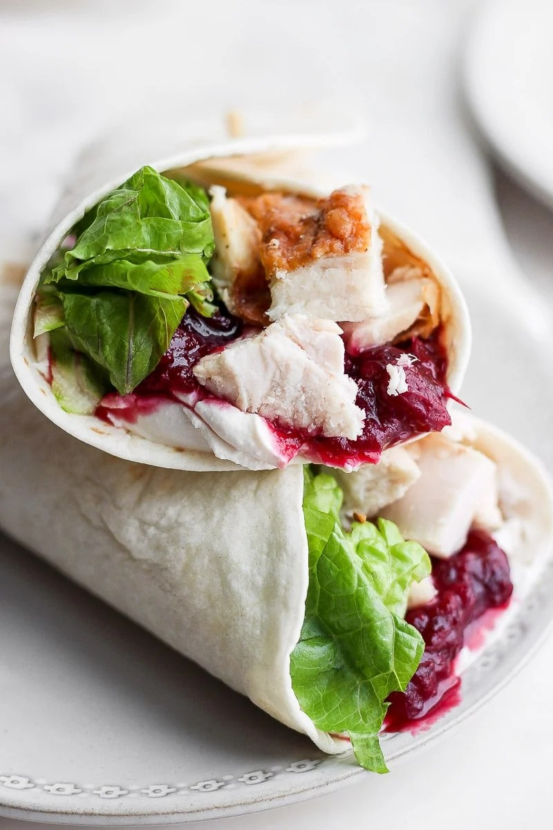 A turkey cranberry wrap on a white plate.
