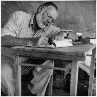 Ernest_Hemingway_Writing_at_Campsite_in_Kenya325px
