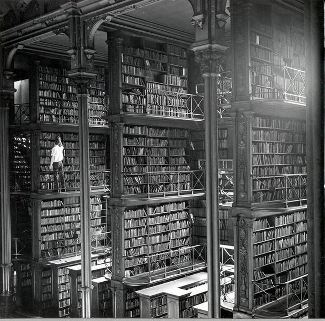 A man browsing for books in Cincinnati's cavernous old main library. The library was demolished in 1955.