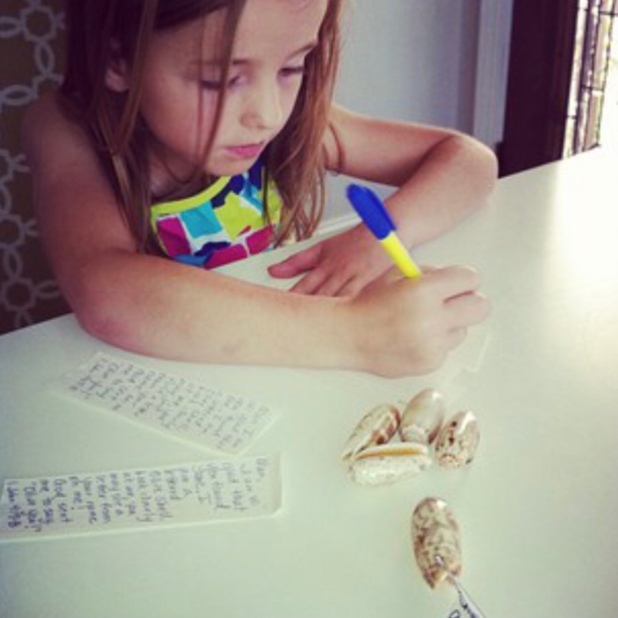 Shows a young girl writing a note for inside a shell