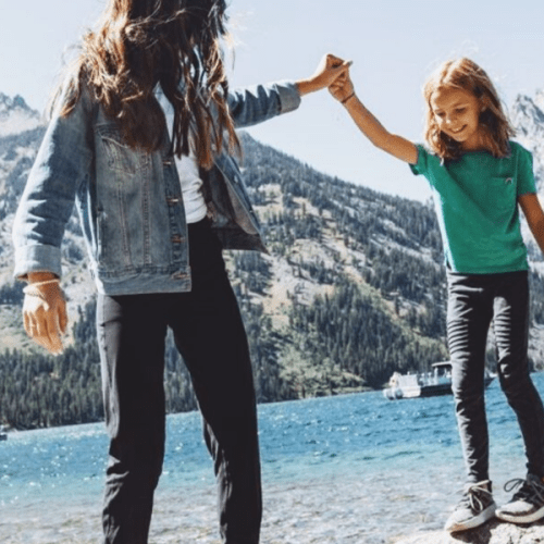 daughters dancing on rocks at beach in front of Jenny Lake