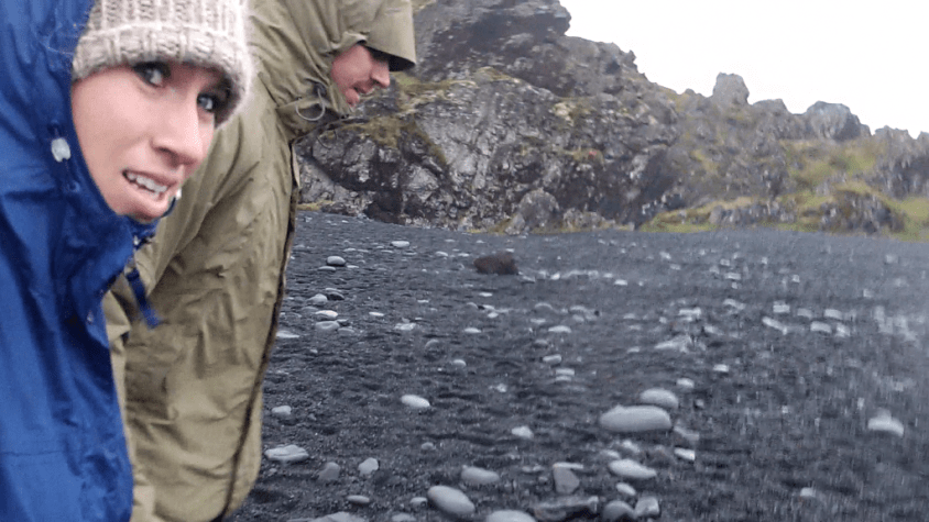 Travel blogging couple returns the cursed rocks of Iceland to the rocky black sand beach.
