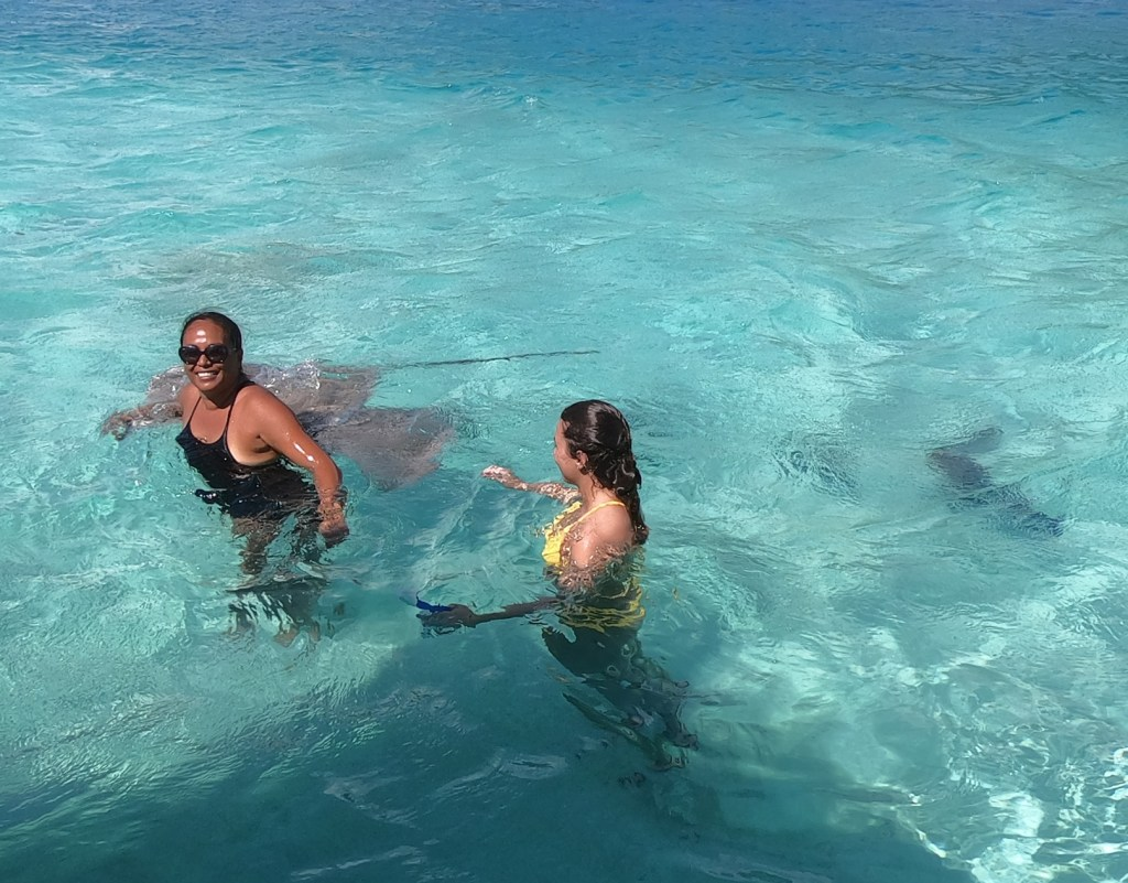 Captain Taina and travel blogger Amanda in the ocean in Moorea with sting rays. One of the best tours in Moorea is a snorkel with Captain Taina.