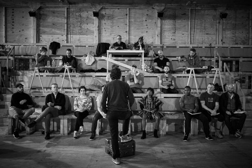 Sam Gold speaks to the cast and crew during a rehearsal break. From the first row, sitting left to right: Anthony Michael Lopez, Glenn Fitzgerald, Nikki Massoud, Finn Wittrock (mostly blocked), Marsha Stephanie Blake, David Oyelowo, Daniel Craig, and Matthew Maher. In the second row, from left to right: Kyle Vincent Terry (blocked), David Wilson Barnes, Blake DeLong. Third row, left to right: Dan Soule, Andrew Lieberman, Slate Holmgren, Michael Schantz, and in the top row from left to right: David Zinn and Sarah Laux