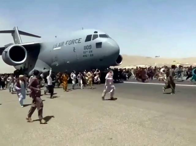 Hundreds of people run alongside a U.S. Air Force C-17 transport plane as it moves down a runway of the international airport, in Kabul, Afghanistan, Monday, Aug.16. 2021. Thousands of Afghans have rushed onto the tarmac at the airport, some so desperate to escape the Taliban capture of their country that they held onto the American military jet as it took off and plunged to death.