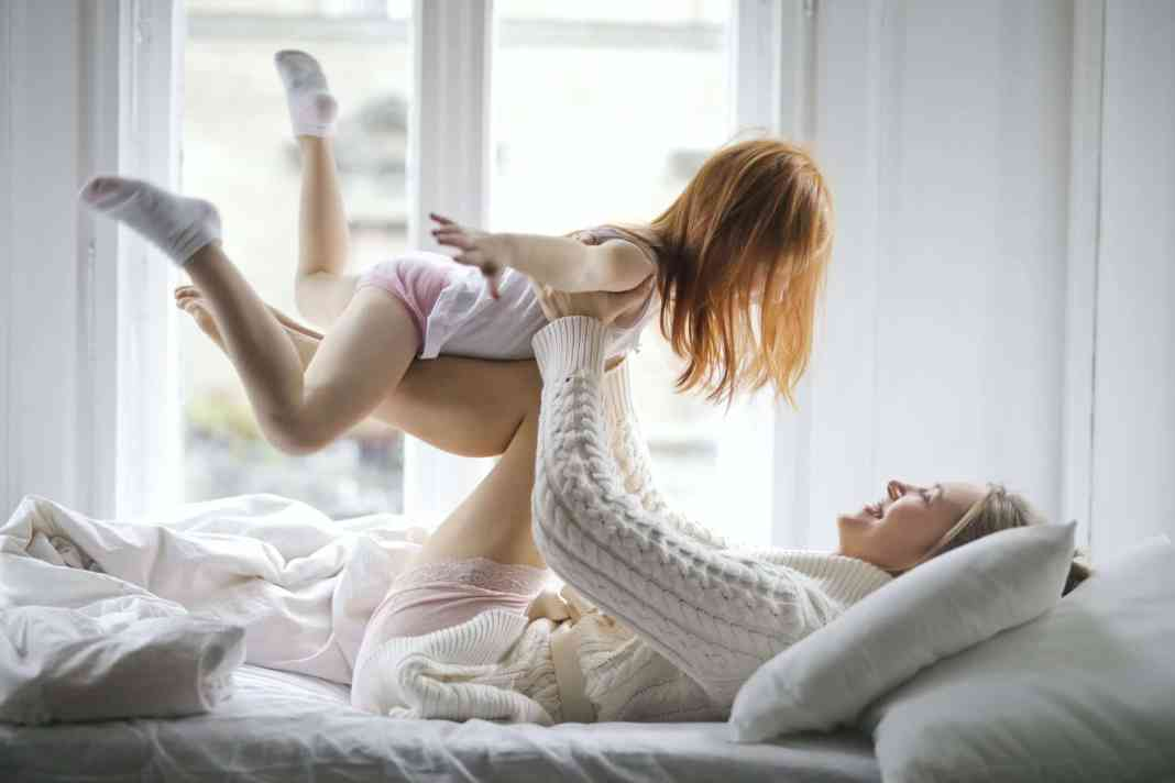 cheerful mother and daughter having fun on bed at home