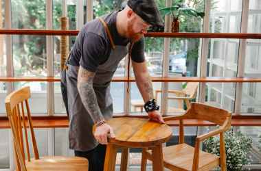 crop cafeteria worker with tattoos putting table on floor