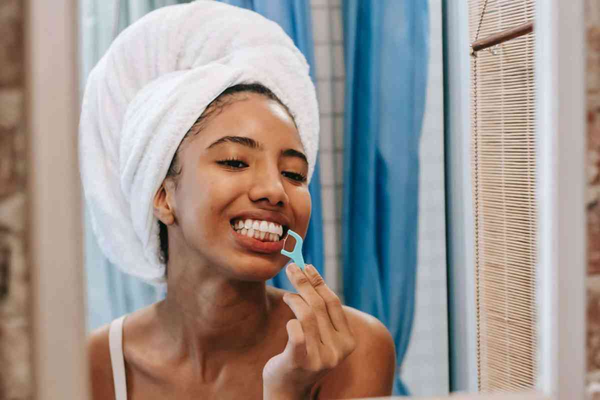 ethnic woman cleaning teeth with dental floss