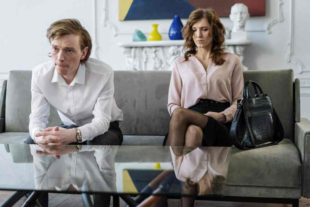 woman in white blazer sitting beside man in white blazer