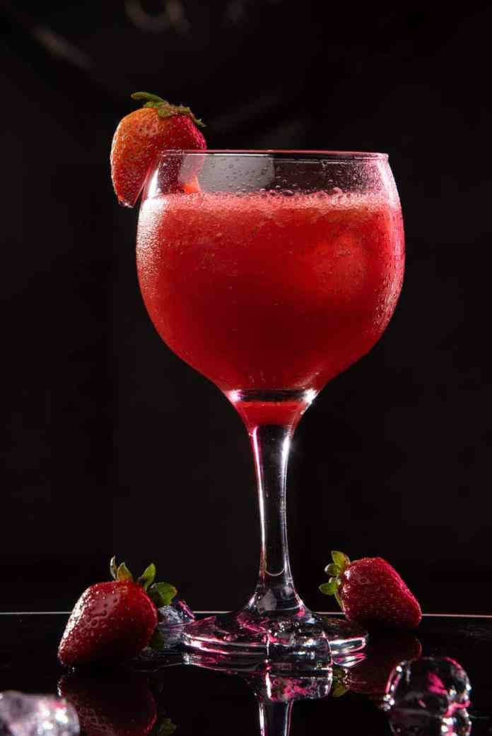 delicious bright strawberry cocktail on black background