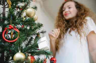 young woman standing near christmas tree decorated with baubles