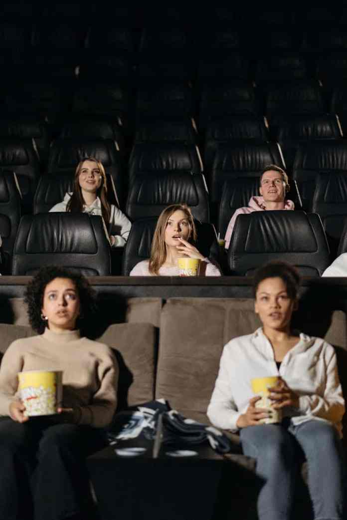 group of people sitting on black leather couch