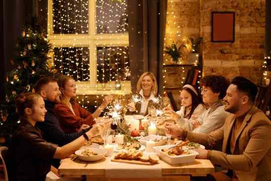 family celebrating christmas while holding burning sparklers