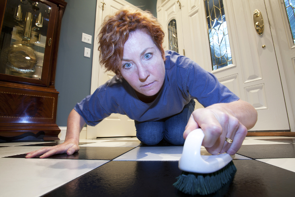 Woman scrubbing the floors on her hands and knees.