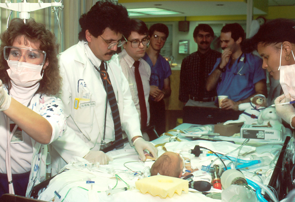 Child in hospital surrounded by doctors