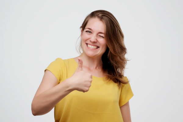 Woman giving thumbs up on white background.