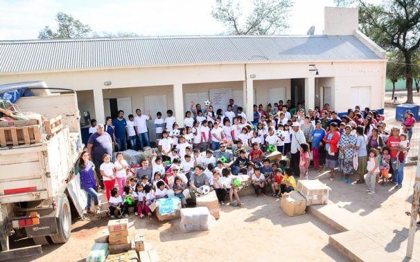 Una foto de grupo con los habitantes de Tres Pozos y los ayudantes de Fútbol por los Chicos frente al colegio del paraje. Fuente: Claudio Barrientes
