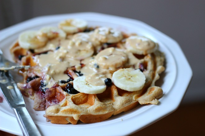 kodiak cake waffle topped with blueberry syrup, peanut butter sauce, and bananas