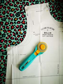 animal print jersey fabric with sewing pattern piece and rotary cutter