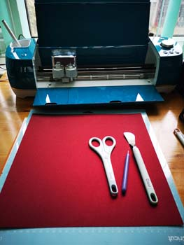 Cricut Air explorer 2 with tools and red glitter cardstock