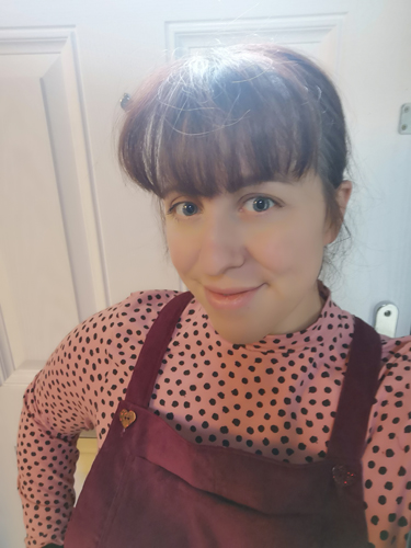 Picture of Sally stood in front of a white door wearing pink with black spot roll neck top with burgundy cord pinafore with heart buttons.