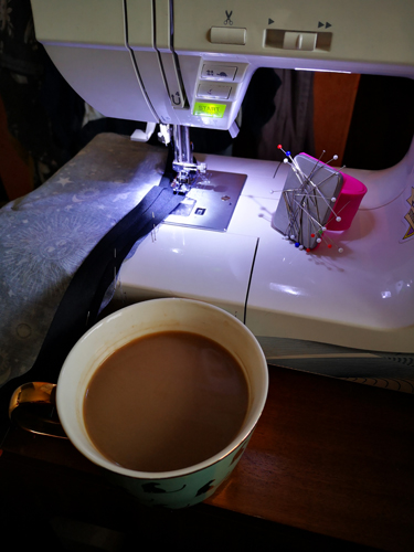 Sewing machine sewing bias binding with cup of coffee in front of it and magnetic pin cushion to the side