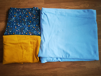 Flat lay of Blue french terry, yellow french terry and floral jersey placed on wooden flor.