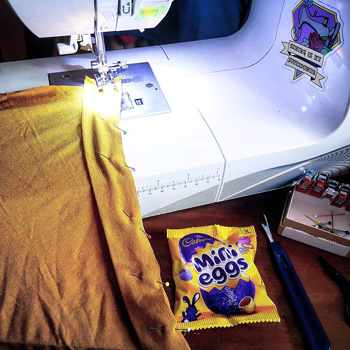 Sewing Machine With Yellow Viscose Jersey With Neckband Pinned In Place, Packet of Mini Eggs, Seam Ripper And Box Of Pins. March Sewing