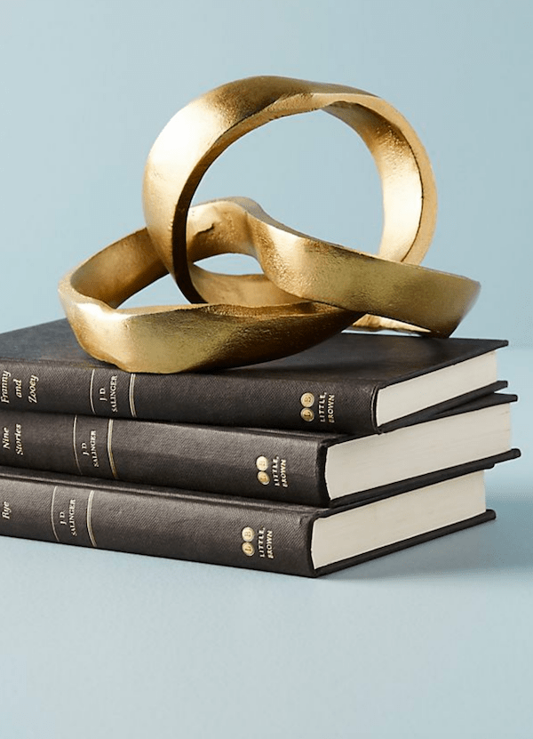 brass knot object on stack of books