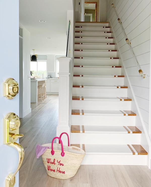 Our Beach House front stair case painted white with lucite bannister