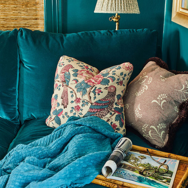 throw pillow vignette on blue velvet couch by Caroline Gidiere Interiors