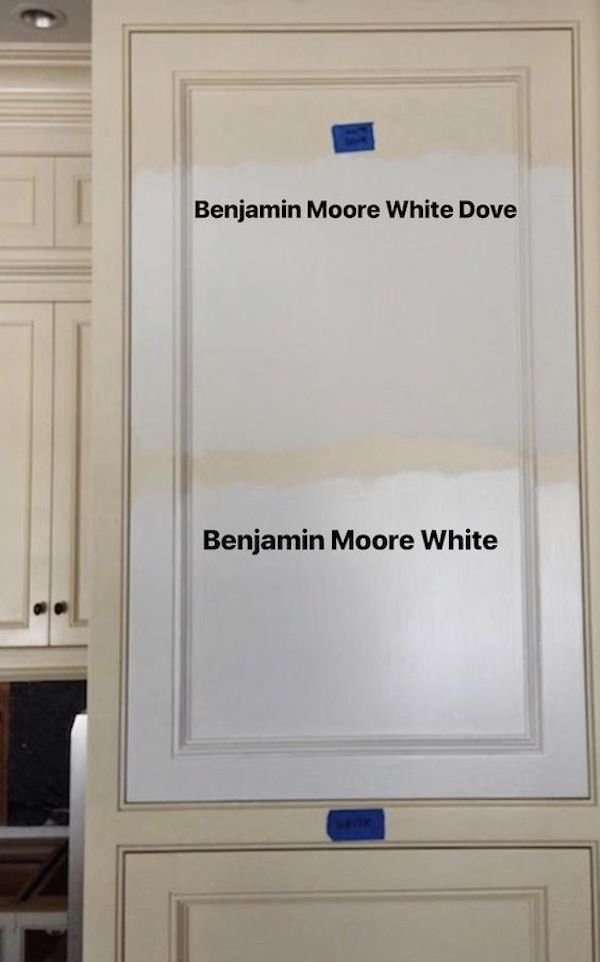 examples of white wall paint samples on a kitchen cabinet